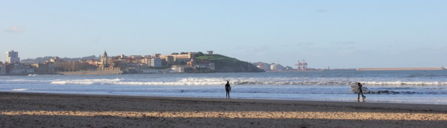 The seafront at Gijón with the casco viejo shining in the distance.